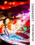 Small photo of Details of a Bright and Colorful Pinball Arcade Game Board lid with neon lights in a gaming room