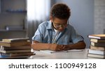 clever male pupil doing math... | Shutterstock . vector #1100949128