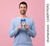 man with blue sweater holding... | Shutterstock . vector #1100979392