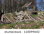 Construction site in old village with rocks and logs - stock photo