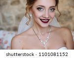 Small photo of A beautiful bride and a dress with open shoulders. A close-up shot of a girl with a delicate eye makeup and red lips smiles. Light curls of hair, earrings and a thin necklace emphasize the neck