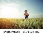 farmer standing in a wheat field | Shutterstock . vector #1101126482