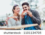 couple eating pizza outdoors... | Shutterstock . vector #1101134705