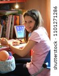 Small photo of smiling little girl in the bedroom with dolly and tablet