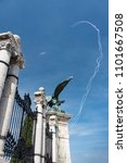The statue of bronze eagle on the gate of Castle Hill and the airplane perfoms a trick releasing smoke in Budapest on 1-st May 2018