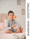 Small photo of boy brunet sits in bed with orange in hands and smiles