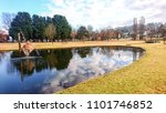 Reflections of park and sky in pond, Armidale, Australia