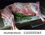 whole raw lamb and knife on the ... | Shutterstock . vector #1102035365