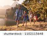 children walk by lake with... | Shutterstock . vector #1102115648