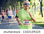 mature runners running in a race | Shutterstock . vector #1102139225