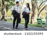 Small photo of Business Couple talking outdoors and walking in a park