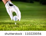 hand hold golf ball with tee on ...
