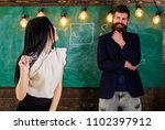 Small photo of Lady teacher and bearded hipster schoolmaster working together in school. Generation concept. Man with beard and young lady teacher stand in classroom, chalkboard on background.