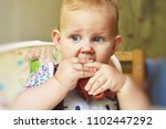 baby is drinking from a cup.... | Shutterstock . vector #1102447292