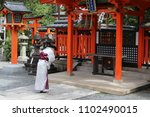 Stock photo woman in a kimono bowing in prayer in a japanese shinto shrine fushimi inari shrine 1102490015