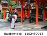 Stock photo woman in a kimono bowing in prayer in a japanese shinto shrine fushimi inari shrine 1102490015