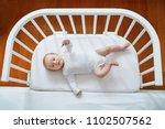 baby girl lying in co sleeper... | Shutterstock . vector #1102507562