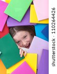 Covered by too much information - young girl emerging from beneath books - stock photo