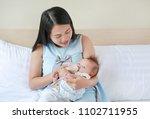 beautiful asian mother feeding... | Shutterstock . vector #1102711955