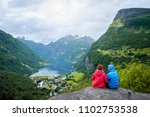 couple sitting on a rock with... | Shutterstock . vector #1102753538