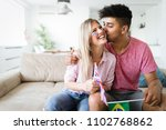 excited couple watching tv... | Shutterstock . vector #1102768862