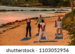 Small photo of Balaclava, Mauritius - September 21, 2017: unidentified adults take part in a yoga cession on the beach at sunset image with copy space in landscape format
