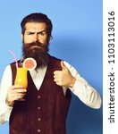 Small photo of handsome bearded man with long beard and mustache has stylish hair on serious face holding glass of alcoholic cocktail in vintage suede leather waistcoat on blue studio background.