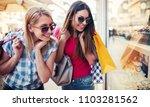 two smiling women enjoying in... | Shutterstock . vector #1103281562