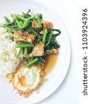Small photo of Thai Food Fried Morning Glory with Crispy or Grounded Pork in chilli and Thai style fried egg in white dish on white background. Thai street food : Pad pak bung fai dang moo krob