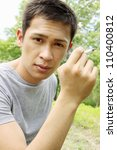 Asian young man holding a cigarette in his hand - stock photo