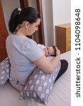 mother breastfeeding baby on... | Shutterstock . vector #1104098648