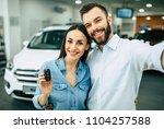 family selfie in dealership.... | Shutterstock . vector #1104257588