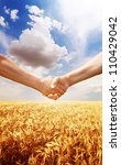 Farmers handshake at wheat field background. - stock photo