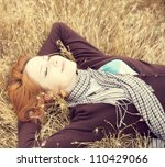 Young beautiful girl lying at yellow autumn field. - stock photo