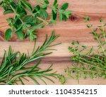 wooden board with fresh herbs.... | Shutterstock . vector #1104354215