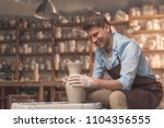 smiling man at a potter's wheel ... | Shutterstock . vector #1104356555