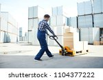 young worker pushing load cart... | Shutterstock . vector #1104377222