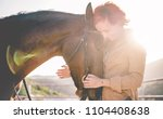 Stock photo young farmer woman hugging her horse concept about love between people and animals focus on pet 1104408638