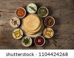 hummus snacks on a wooden board ... | Shutterstock . vector #1104424268
