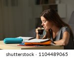 Small photo of Side view portrait of a studious student studying drinking coffee late hous in the night at home