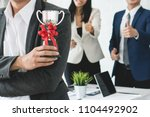 worker holding trophy prize for ... | Shutterstock . vector #1104492902