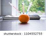 Syringe Sticked Into Orange On...