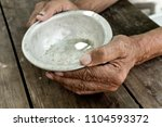the poor old man's hands hold... | Shutterstock . vector #1104593372