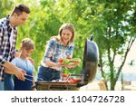 happy family having barbecue... | Shutterstock . vector #1104726728