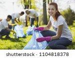 volunteering in park. joyful... | Shutterstock . vector #1104818378