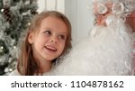 Small photo of Cute little girl singing Christmas song together with Santa Claus