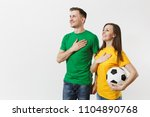 Small photo of Emotional couple, woman man, football fans in yellow green t-shirt cheer up support team with soccer ball singing national country anthem isolated on white background. Sport leisure lifestyle concept
