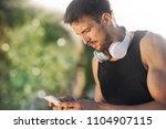 male runner typing something on ... | Shutterstock . vector #1104907115