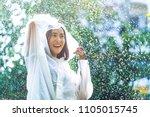 rainy day asian woman wearing a ... | Shutterstock . vector #1105015745