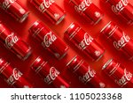Small photo of Lvov, Ukraine - January 23, 2018. Close-up of Coca Cola drink jars lying on paper background. Texture. Top view